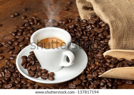 coffee cup with burlap sack of roasted beans and scoop - stock photo