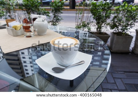 coffee cup with cappuccino on a table in cafe