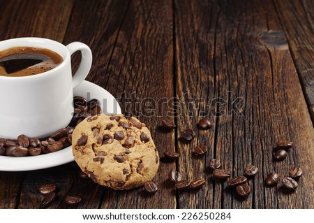 Coffee cup with chocolate cookie on dark wooden background - stock photo