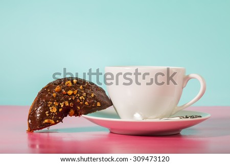 Coffee cup with chocolate donuts on pastel blue background - stock photo