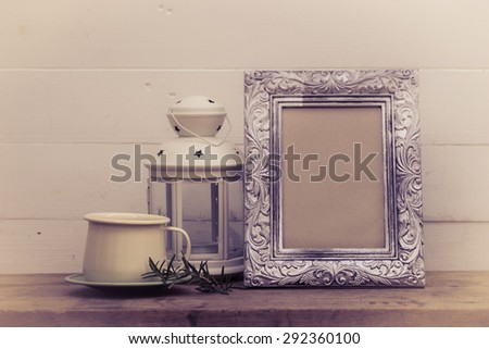 Coffee cup with Christmas lantern and vintage silver frame abstract background on white boards - stock photo
