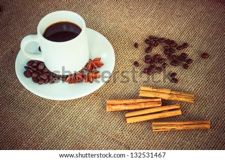 Coffee cup with cinnamon, anise and beans on sack