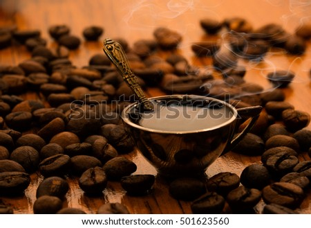 Coffee cup with coffee and spoon in coffee beans on a wooden table close-up