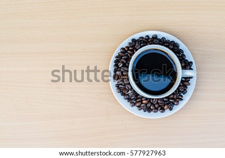 Coffee cup with coffee bean on wooden table view from top