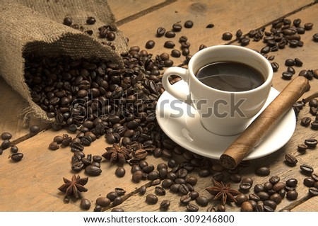 Coffee cup with coffee beans, cigar on bagging and wood. - stock photo