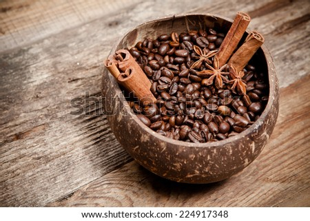 Coffee cup with coffee beans, cinnamon, star anise on old wooden table. - stock photo