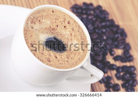 Coffee cup with coffee beans. Cross processed image with shallow depth of field