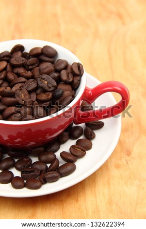 Coffee cup with coffee beans on a light wooden background