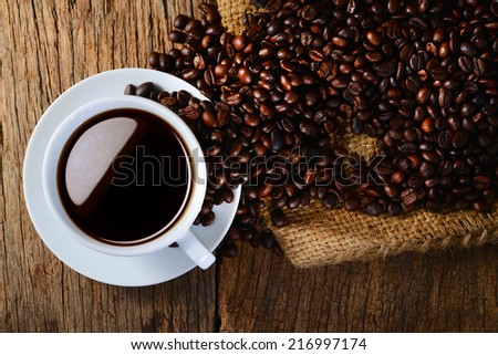 Coffee cup with coffee beans on burlap bag - stock photo