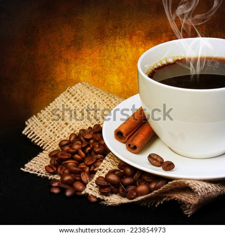 Coffee cup with coffee beans on burlap over dark