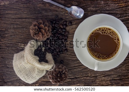 Coffee cup with coffee beans on the old wooden floor