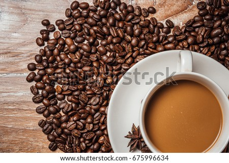 coffee cup with coffee beans,on wood table.