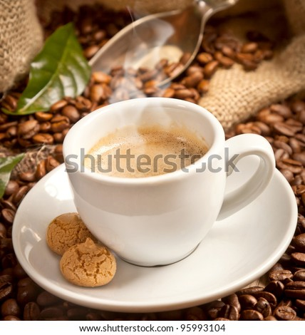 Coffee cup with coffee-tree leaves and fresh coffee beans on brown - stock photo