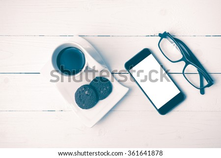 coffee cup with cookie,phone and eyeglasses on white wood table vintage style