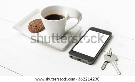 coffee cup with cookie,phone and key on white wood table