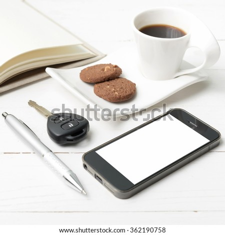 coffee cup with cookie,phone,open notebook and car key on white wood table