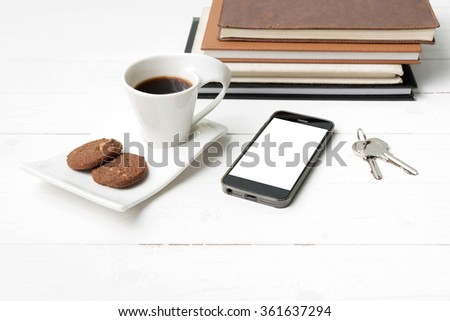 coffee cup with cookie,phone,stack of book and key on white wood table