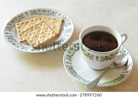 Coffee cup with crackers on marble table
