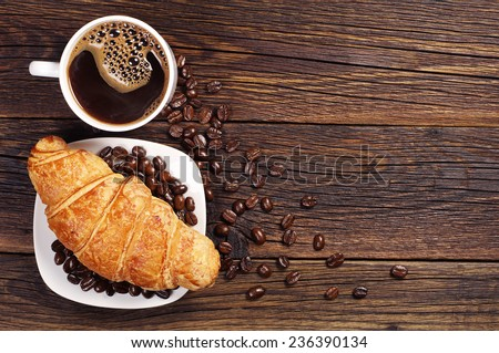 Coffee cup with croissant for breakfast on a dark wooden table, top view