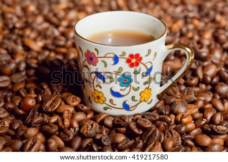 Coffee cup with floral patterns and background with coffee beans.  - stock photo