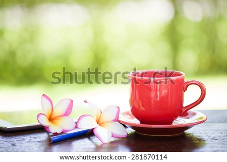 Coffee cup with flowers on wooden table - stock photo