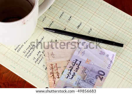 Coffee cup with general ledger sheet showing journal entries and black ballpoint pen with Moroccan one hundred dirham bill and twenty dirham bill - stock photo