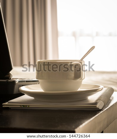 coffee cup with laptop and notebook onthe table in bed room - stock photo
