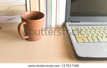 coffee cup with laptop and stack of books on wood table