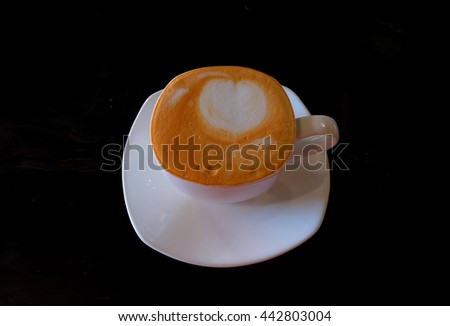 Coffee cup with latte art on black background