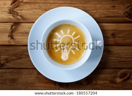 Coffee cup with light bulb idea in the froth concept for ideas, creativity and innovation - stock photo