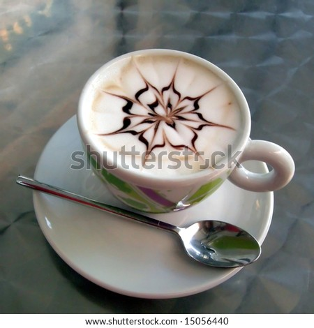 Coffee cup with milk and chocolate decoration on top