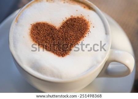 Coffee cup with milk and heart shape - stock photo