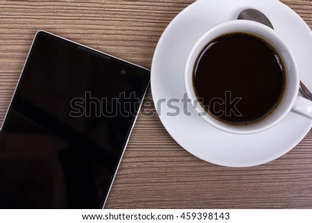 Coffee cup with mobile phone and tablet on a woodn surface