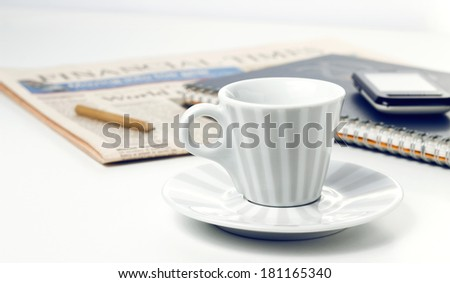 coffee cup with newspaper and smart phone on white office desk - stock photo