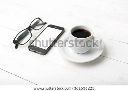 coffee cup with phone and eyeglasses on white wood table