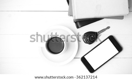coffee cup with phone,car key and stack of book on white wood table black and white color