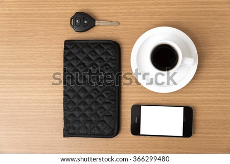 coffee cup with phone car key and wallet on wood background