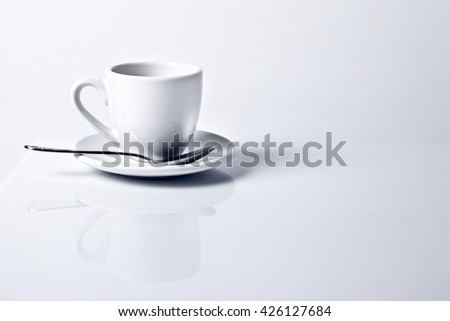 Coffee cup with plate and spoon on white shiny background