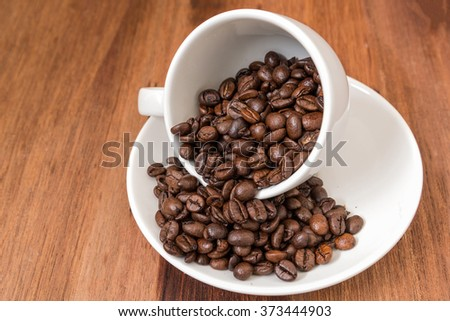 coffee cup with roasted coffee beans on wooden background