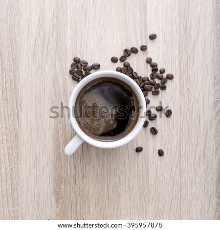 Coffee cup with roasted coffee beans on wooden background. View from top - stock photo