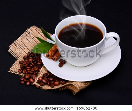 Coffee cup with saucer and coffee beans on burlap over black background  - stock photo