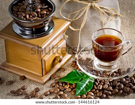Coffee cup with saucer, coffee mill, bag and coffee beans on the sackcloth - stock photo