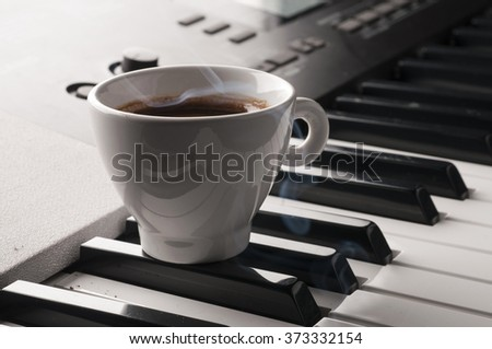 Coffee cup with smoke on  a piano keyboard