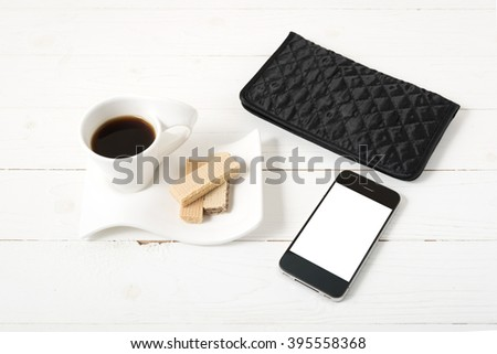 coffee cup with wafer,phone,wallet on white wood background