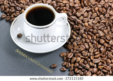 coffee cup with whole coffee beans and German menu (translation: meals and drinks)