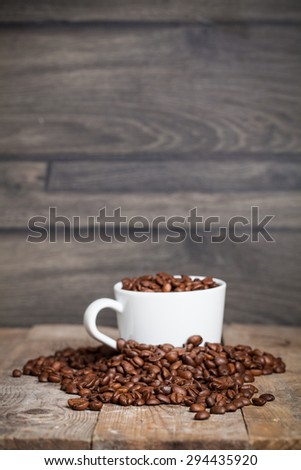 Coffee cup with wooden background with coffee beans