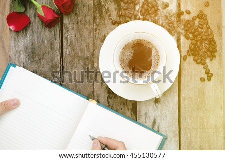 Coffee cup with writing notes on old wood background