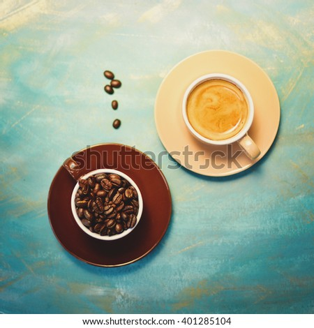 Coffee cups and coffee beans on blue background. Top view. - stock photo