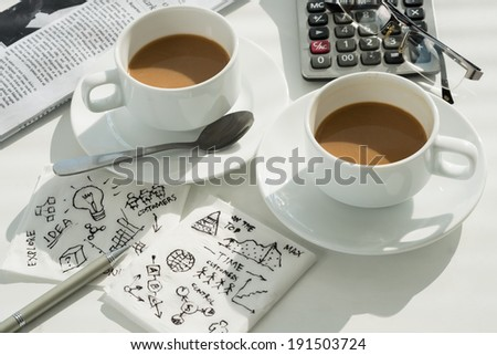 Coffee cups and napkins with business ideas - stock photo