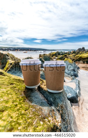 Coffee cups on the beach in trevone cornwall england uk.